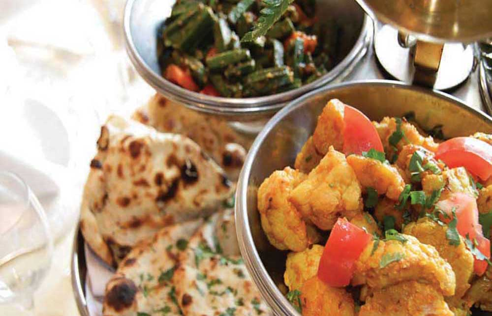 A picture of an Indian meal including cauliflower and naan bread