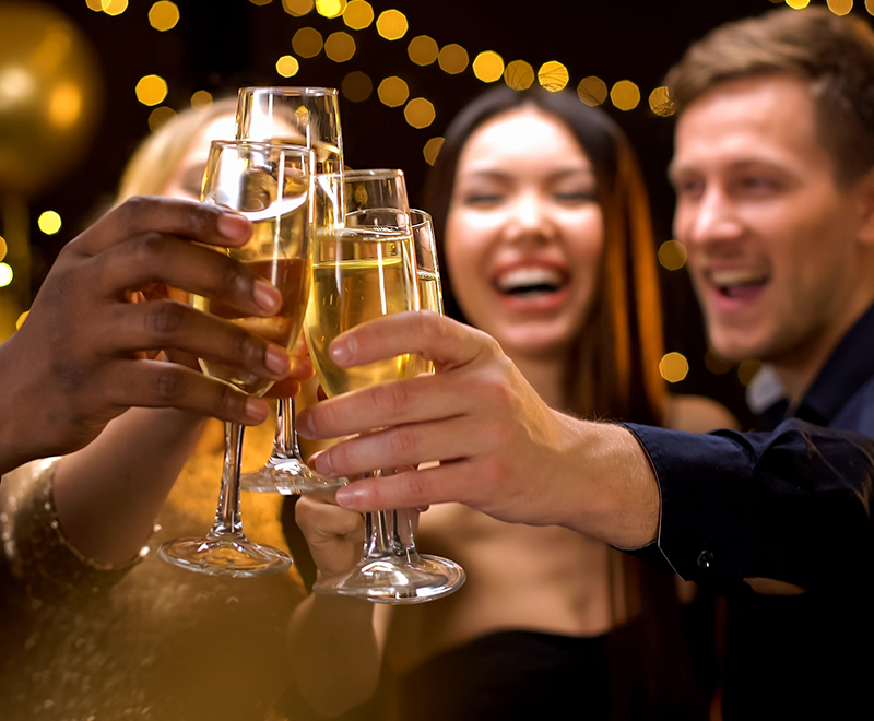 photo of four attendees celebrating with champagne
