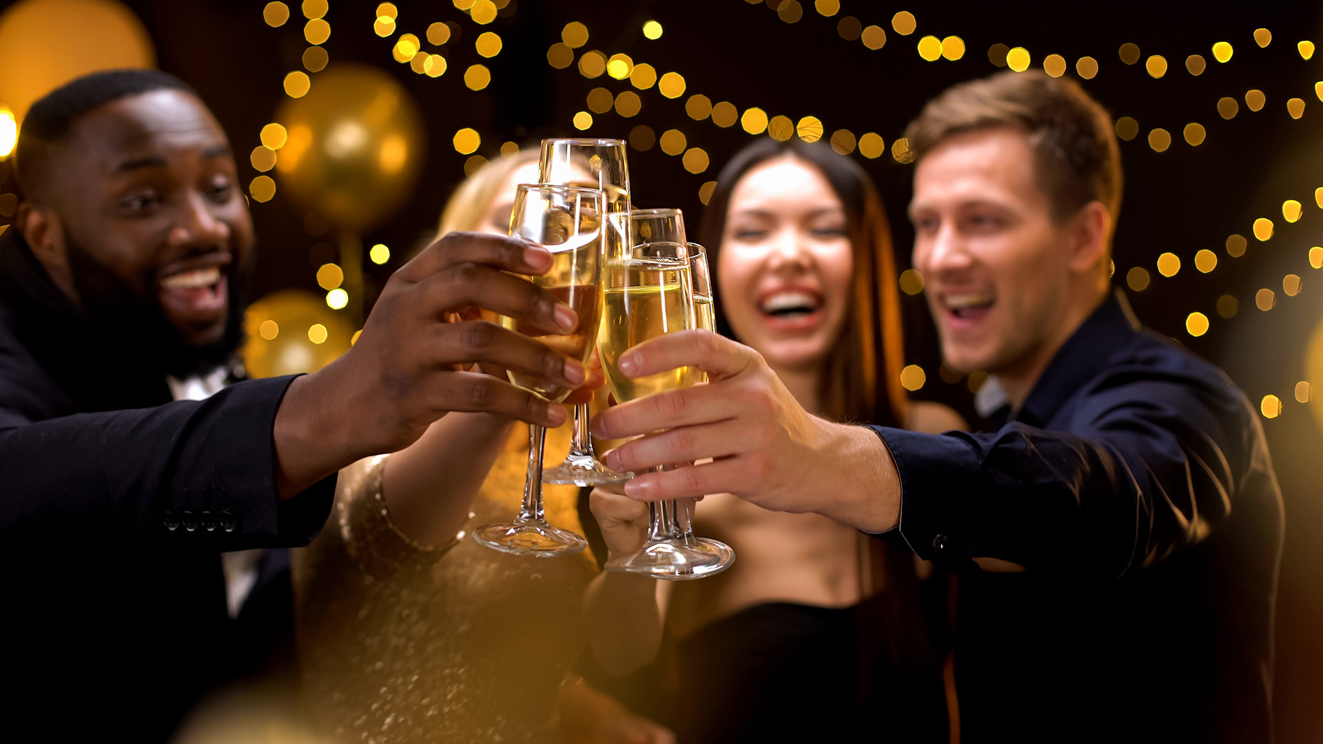 Photo of four friends celebrating with champagne