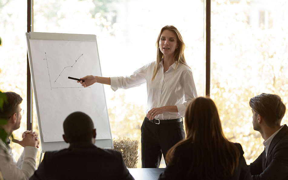 Woman presenting flip chart to small group