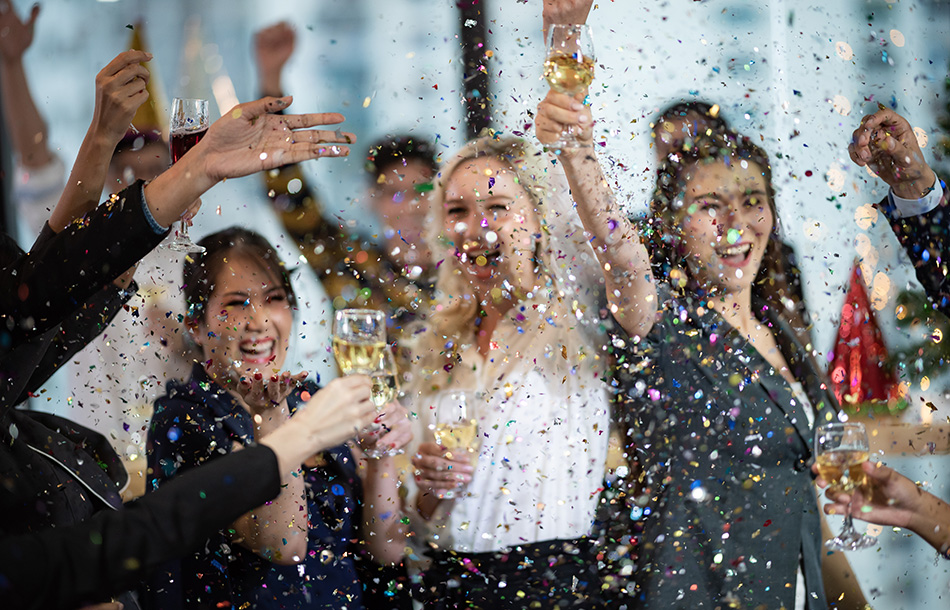 Group of people celebrating with confetti and champagne